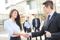 Welcome to our team young businesswoman and businessman shaking hands in front of the company while in the background them Stock Images