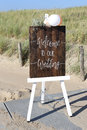 Welcome to our wedding easel with wooden sign in front of dunes Royalty Free Stock Photos