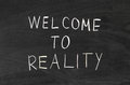 Welcome to reality word handwritten on the school blackboard Stock Photography
