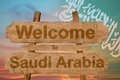 Welcome to Saudi Arabia sign on wood background with blending national flag