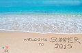 Welcome to summer written on a tropical beach under clouds Royalty Free Stock Photography