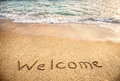 Welcome word on the sand beach near ocean Royalty Free Stock Photos