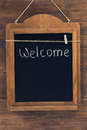Welcome written with chalk on aged blackboard hanging on wooden wall Royalty Free Stock Photo