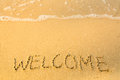Welcome, written in sand on beach texture, soft wave of the sea. Travel. Royalty Free Stock Photo