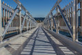 Welded aluminum walkway a long all gangplank for people to walk to a dock Stock Photos