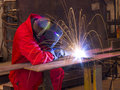 Welder bends to cut metal beam with orange sparks. Stock Photography