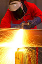 Welder bends to cut metal beam with orange sparks. Royalty Free Stock Images