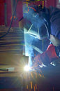 Welder with protective mask welding metal and sparks Stock Image