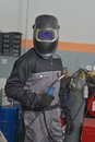Welder smiling in gray work wear and helmet at work place Royalty Free Stock Photo