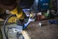 Welder welding steel base for new stool.