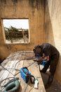Welder at work in old house in africa working on metal tubes the bush mali Stock Images