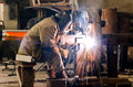Welder at work sparks and drops of molten metal during of Royalty Free Stock Photography