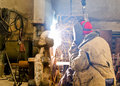 Welder at work sparks and drops of molten metal during of Stock Photography