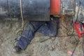 Welder worker grinding the weld in trench under pipeline
