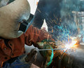 Welding welder at work on an outdoor pipeline project Stock Photo