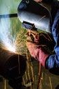 Welding worker doing welding at pipe in workshop Stock Photo