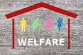 Welfare concept on wooden background with coloured home and old man disabled pregnant and women with baby Stock Photos
