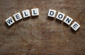 Well done written in tiles on wooden surface Stock Photography