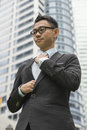 Well dressed asian business man adjusting his neck tie Royalty Free Stock Photo