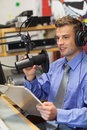 Well dressed happy radio host moderating sitting in studio at college Royalty Free Stock Photo