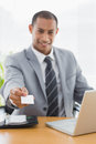 Well dressed man handing his business card at office desk smiling young over in front of laptop Royalty Free Stock Photography