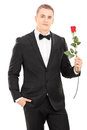 Well dressed man holding a red rose isolated on white background Stock Photo