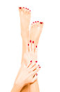 Well groomed female feet and hands with red polish Royalty Free Stock Photography