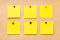 Well ordered yellow post it collection set of six square blank notes affixed by colored pins on a wooden board and ready to take a Stock Photography