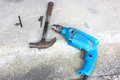 Well used hammer and electric drill on concrete floor of work shop Stock Photo