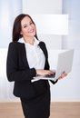 Welldressed businesswoman using laptop in office portrait of young while standing Royalty Free Stock Photo