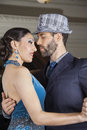 Welldressed dancers performing tango in cafe male and female Royalty Free Stock Photo