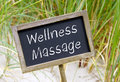 Wellness massage chalkboard or blackboard with text and sand or beach and green grass in the background Stock Images