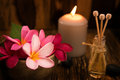 Wellness spa concept candles frangipani flower sandalwood rattan sticks massage table Stock Images