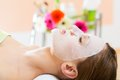 Wellness woman getting face mask in spa receiving facial for clean skin Stock Image
