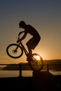 West bay united kingdom july bmx rider silhouetted sunset hops off concrete walkway harbour wall west bay dorset Stock Photos