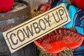 Western decor with Cowboy up sign and painted red vintage tractor seat Royalty Free Stock Photo