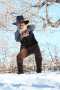 Western gunslinger a cowboy against a bright blue sky he s firing his pistol and a gun fight Stock Image