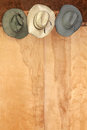 Western hat decor cowboy of well worn cowboy hats hanging on a wood grain textured wall with copy space Royalty Free Stock Images