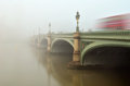 Westminster bridge in fog a thick envelops and big ben and the houses of parliament disappear shrouded Stock Image