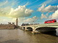 Westminster bridge and houses of parliament at sunset london b beautiful view with red bus crossing the Royalty Free Stock Photo