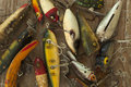 Wet antique fishing lures viewed from above on a rough wood surf Royalty Free Stock Photo