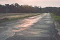 Wet asphalt road with sun reflections vintage and trees photography effect Royalty Free Stock Image