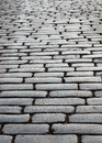 Wet block stones of sett paving the pavement is receding into the distance focus is on front Royalty Free Stock Image