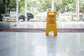 Wet floor sign on the floor near an outdoor parking Royalty Free Stock Image
