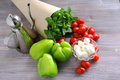 Wet fresh basil, cherry tomatoes, green sweet pepper, mozzarella cheese and oil jug on a wooden table Royalty Free Stock Photo