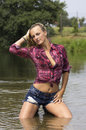 Wet girl beautiful blonde posing in the river with her clothes on Royalty Free Stock Photography