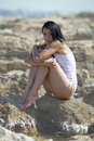 Wet girl in white tank top sitting on rocky beach at the sea Royalty Free Stock Photos