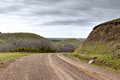 Wet gravel road winding around green hills. Royalty Free Stock Photo
