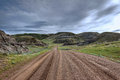 Wet gravel road winding through grass covered hills under stormy sky Royalty Free Stock Photo