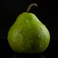 Wet green pear fading into black background Royalty Free Stock Photos